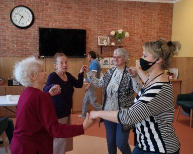 Terapeutka Beata Gadomska i trzy seniorki tańczą w kółeczku. Trzymają się za ręce.