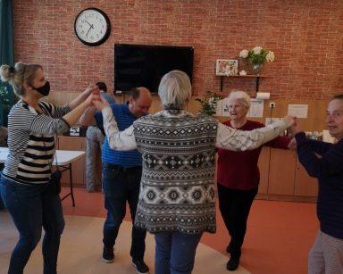 Terapeutka Beata Gadomska, trzy seniorki i senior tańczą w kółeczku. Trzymają się za ręce.