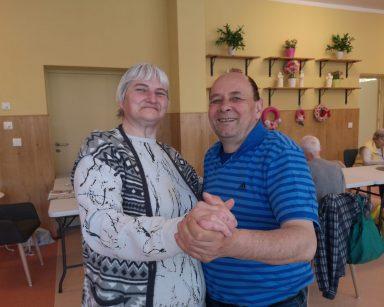 Senior i seniorka tańczą trzymając się za ręce. W tle seniorzy siedzący przy stołach.