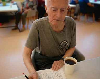 Senior przy stole rozwiązuje wykreślankę. Obok stoi kubek z kawą. W tle siedzą inni seniorzy.