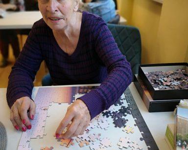 Uśmiechnięta seniorka układa puzzle. W tle siedzą inni seniorzy.