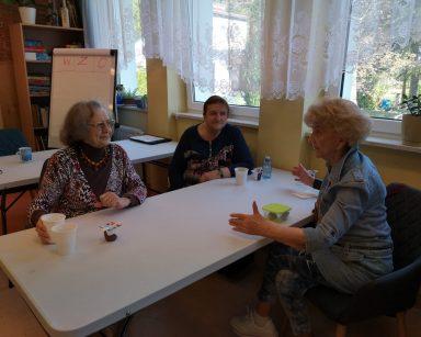 Trzy seniorki siedzą przy stole i rozmawiają. Na blacie kubki z kawą.
