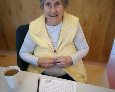 Seniorka uśmiecha sią do zdjęcia. Przed nią na blacie kubek z kawą, wykreślanka i ołówek.