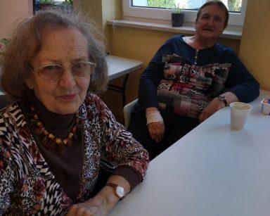 Dwie seniorki siedzą przy stole. Przed nimi kubki z kawą.