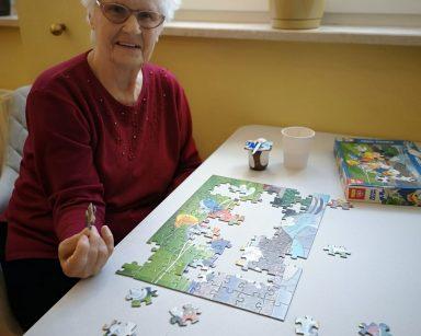 Uśmiechnięta seniorka układa puzzle. Na blacie układanka i kubek z kawą.