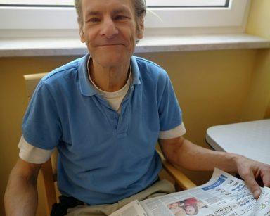 Uśmiechnięty senior siedzi na krześle. Na kolanach trzyma rozłożoną gazetę.