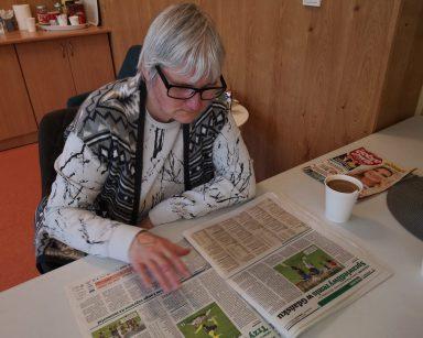 Seniorka siedzi przy stole i czyta gazetę. Na blacie oprócz gazety kubek z kawą.