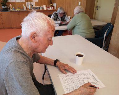 Senior siedzi przy stole i rozwiązuje wykreślankę. Na blacie stoi kubek z kawą. Przy dalszym stole siedzą seniorki.