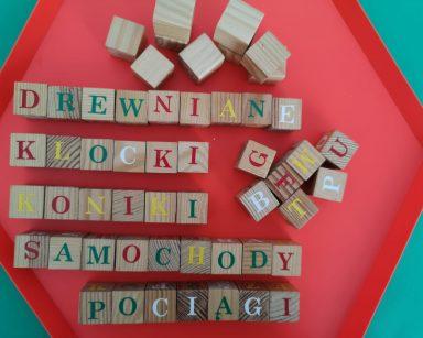 Widok z góry. Drewniane klocki z kolorowymi literami. Są ułożone w napisy: drewniane klocki, koniki, samochody, pociągi.