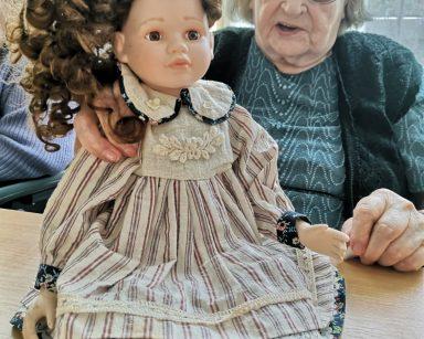 Seniorka trzyma lalkę. Lalka ma brązowe, kręcone włosy. Jest ubrana w sukienkę z kołnierzem i pasisty fartuszek.
