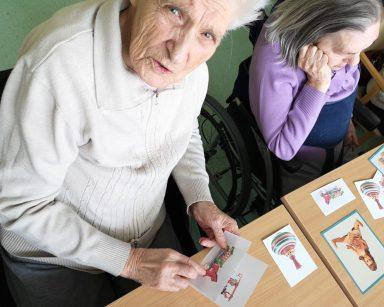 Dwie seniorki siedzą przy stole i oglądają rozłożone obrazki. Na obrazkach drewniane zabawki, kolorowe bączki, lalki.
