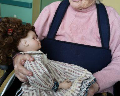 Seniorka trzyma na kolanach lalkę. Lalka ma brązowe, kręcone włosy. Jest ubrana w sukienkę z kołnierzem i pasisty fartuszek.