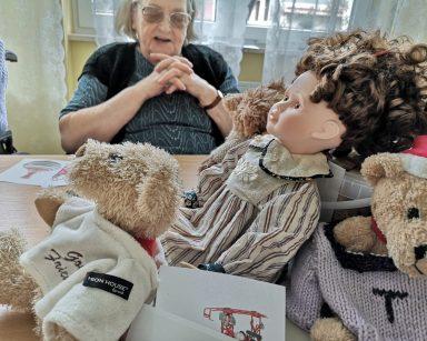 Przy stole siedzi uśmiechnięta seniorka. Przed nią na blacie zabawki: lalka, misie.