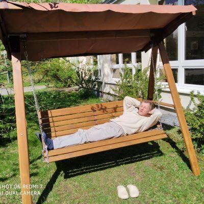 Słoneczny dzień. Senior leży i odpoczywa na drewnianej huśtawce.