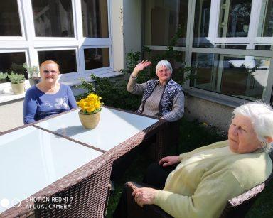 Słoneczny dzień. Trzy seniorki siedzą przy stole przed ogrodem zimowym i rozmawiają.