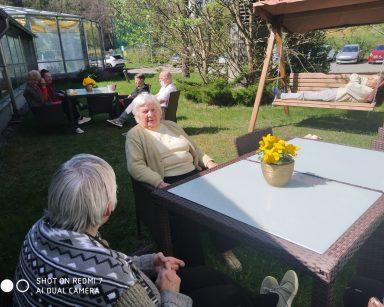 Słoneczny dzień, trawnik przed ogrodem zimowym. Seniorzy siedzą i rozmawiają przy stolikach. Jeden senior leży na huśtawce.