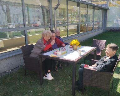 Słoneczny dzień, trawnik przed ogrodem zimowym. Seniorzy siedzą i rozmawiają przy stoliku.