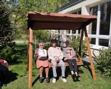 Słoneczny dzień, trawnik przed ogrodem zimowym. Troje seniorów siedzi razem na drewnianej huśtawce.