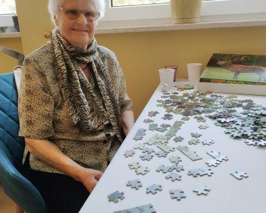 Uśmiechnięta seniorka siedzi przy stole. Na blacie częściowo ułożone puzzle.