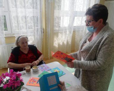 Kierowniczka Mariola Ludwicka odczytuje życzenia z kartki. Przy stole siedzi seniorka. Na blacie ozdobione kolorowe kartki.