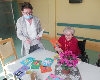 Kierowniczka Mariola Ludwicka odczytuje życzenia z kartki. Obok niej siedzi roześmiana seniorka. Na blacie kolorowe kartki.