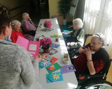 Kierowniczka Mariola Ludwicka odczytuje życzenia z kartki. Przed nią przy stole cztery seniorki. Na blacie kolorowe kartki.