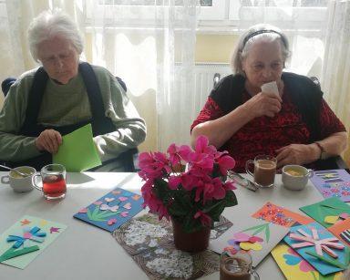 Przy stole siedzą dwie seniorki. Na blacie szklanki z kawą i z herbatą, kolorowe kartki i kwiaty.