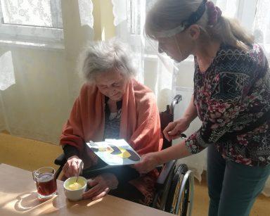 Seniorka siedzi przy stole. Koło niej stoi terapeutka Ewa Rodziewicz i pokazuje kartkę z naklejoną kolorową pszczołą.