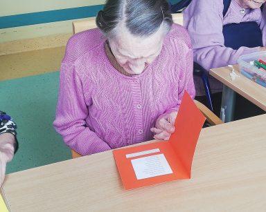 Seniorka siedzi przy stole. Nachyla się nad otwartą czerwoną kartką i czyta zamieszczony wewnątrz tekst.