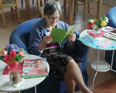 Seniorka siedzi w fotelu, ogląda kolorową kartkę w serduszka. Obok, na stolikach inne kolorowe kartki, kwiaty, czasopisma.