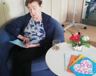 Seniorka siedzi w fotelu, ogląda kartkę z kolorowymi kwiatami. Obok, na stoliku inne kolorowe kartki, kwiaty, kawa.