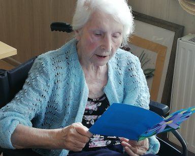 Seniorka trzyma w dłoniach rozłożoną niebieską kartkę z papierowym kwiatem na pierwszej stronie.
