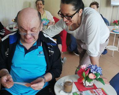 Uśmiechnięta terapeutka Magdalena Poraj-Górska nachyla się nad seniorem. Senior trzyma w dłoniach pomarańczową kartkę.