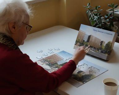 Seniorka układa na stole puzzle. Obok na blacie kubek z kawą.