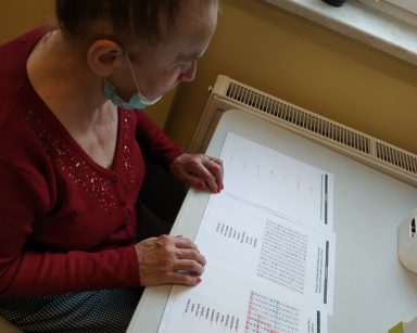 Seniorka siedzi przy stole. Przed nią rozłożone kartki z łamigłówkami.
