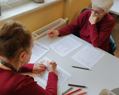 Na przeciwko siebie siedzą seniorki i rozwiązują łamigłówki. Na blacie kartki z łamigłówkami i kolorowe kredki.