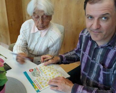 Senior i seniorka wspólnie rozwiązują krzyżówkę.