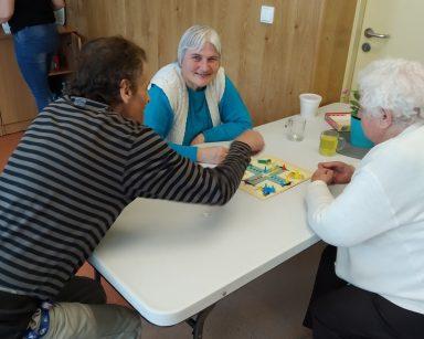 Troje seniorów siedzi przy stole. Graja wspólnie w grę planszową.