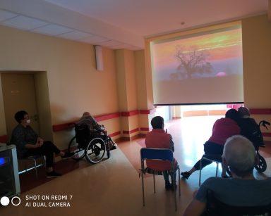 Ciemny korytarz. Na ekranie projektora krajobraz podczas zachodu słońca. Przed ekranem seniorzy i pracownicy.