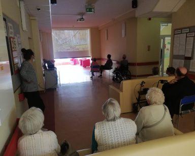 Korytarz. Seniorzy siedzą na krzesłach i kanapach. Oglądają film. Przed nimi ekran projektora z ujęciem zielonego lasu.