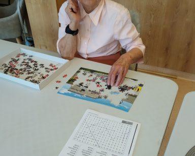 Seniorka uśmiecha się do zdjęcia. Przed nią na blacie częściowo ułożone puzzle i kartka z wykreślanką.