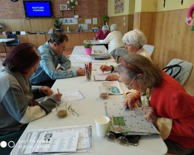 Przy stołach siedzą seniorzy. Rozwiązują różne łamigłówki: krzyżówki, sudoku, wykreślanki.