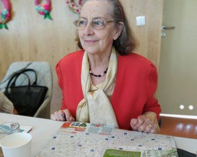 Seniorka siedzi przy stole. Przed nią rozłożona gazeta z krzyżówkami, obok kubek z kawą.