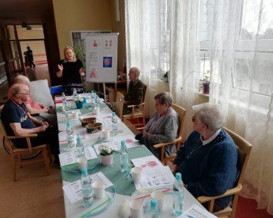 Neurologopedka Ania Szmaja-Wysocka prowadzi spotkanie. Przed nią seniorzy. Za nią tablica z układem oddechowym człowieka.