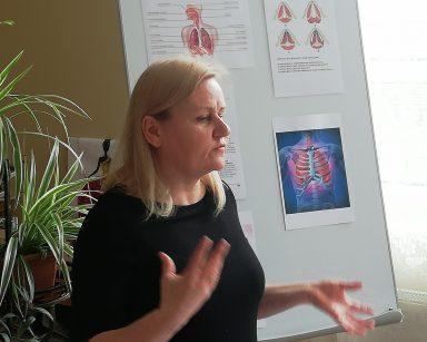 Neurologopedka Anna Szmaja-Wysocka mówi gestykulując. Za nią tablica z obrazkami. Na nich drogi oddechowe człowieka.