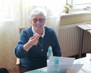 Przy stole siedzi uśmiechnięta seniorka. Wyciąga przed siebie rękę z zapaloną świeczką.