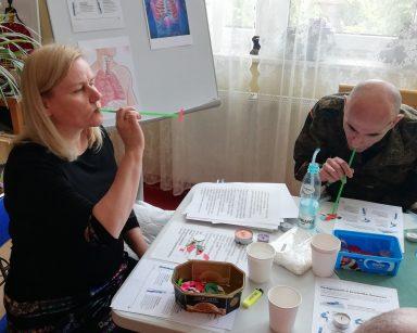 Neurologopedka Anna Szmaja-Wysocka pokazuje seniorom ćwiczenie oddechowe z użyciem słomki. Senior próbuje je wykonać.