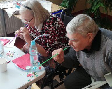 Dwoje seniorów wykonuje ćwiczenie oddechowe używając słomek.