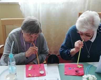 Dwie seniorki wykonuje ćwiczenie oddechowe używając słomek.