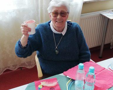 Uśmiechnięta seniorka wznosi kubek z sokiem do toastu.